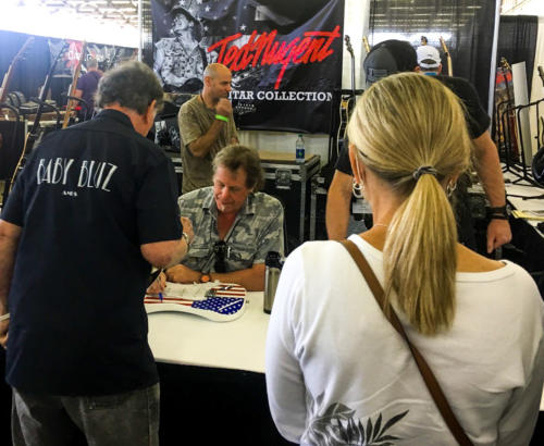 Ted Nugent signs guitar for charity